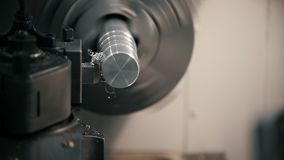 Taglio delle parti di metallo sulla macchina del tornio alla fabbrica, trucioli del metallo, concetto industriale, vista frontale archivi video