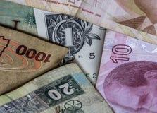 Taglio delle parti delle valute diverse dall'Uganda, U.S.A., Denma fotografia stock