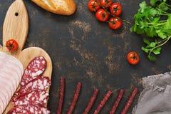 Taglio delle salsiccie varie con i pomodori, baguette su un fondo scuro, spazio per testo Vista da sopra Fotografia Stock Libera da Diritti