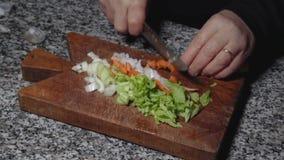 Taglio delle verdure sul tagliere antico MF stock footage
