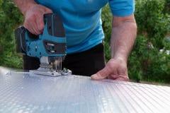 Taglio dello strato del policarbonato dal puzzle della tagliatrice fotografie stock libere da diritti