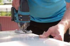 Taglio dello strato del policarbonato dal puzzle della tagliatrice fotografia stock libera da diritti