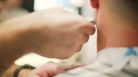 Taglio di capelli maschio con il rasoio elettrico Parrucchiere professionista che taglia il rasoio elettrico dei capelli Fine in  stock footage
