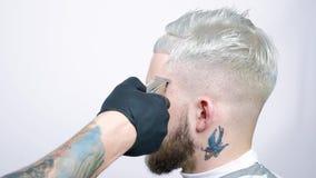 Taglio di capelli in parrucchiere con un rasoio elettrico Ritratto di un uomo biondo stock footage