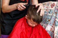 Taglio di capelli per il ragazzo a casa con la macchina Immagine Stock