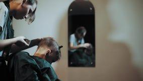 Taglio di capelli per il regolatore del ragazzo per capelli ed il pettine al parrucchiere video d archivio