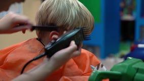 Taglio di capelli di un ragazzino in un salone di lavoro di parrucchiere del ` s dei bambini video d archivio