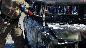 Taglio di Firefighers con una taglierina idraulica di salvataggio ad una liberazione video d archivio