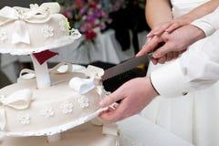 Taglio di una fetta di torta di cerimonia nuziale Fotografia Stock
