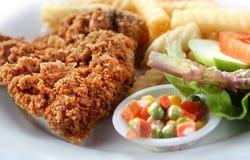 Taglio e chip del pollo fritto con insalata Immagini Stock