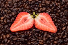 Taglio fresco della fragola a metà contro lo sfondo dei semi di cacao torrefatti fotografia stock libera da diritti