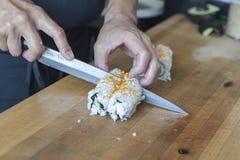 Taglio manuale del cuoco unico di sushi un rotolo dei sushi fotografia stock