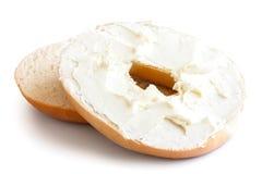 Taglio normale del bagel a metà e diffusione con formaggio cremoso O isolata immagini stock