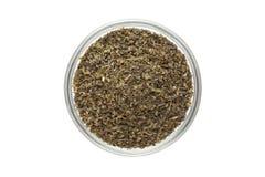 Taglio organico della bustina di tè del tè verde (camellia sinensis), foglie secche, in ciotola di vetro Fotografia Stock