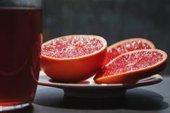 Taglio rosso fresco del pompelmo nei pezzi che scintillano con il succo in sunli fotografia stock