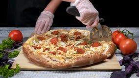 Taglio saporito della pizza con il coltello del rullo Pagina Il cuoco unico taglia la pizza sul vassoio di legno con il coltello  video d archivio
