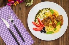 Tagliolini met vlees in tomatensaus, olijven en spinazie Houten achtergrond Close-up Hoogste mening royalty-vrije stock foto's