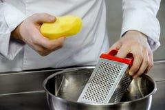 Tagliuzzamento delle patate su una grattugia Fotografia Stock