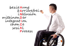 Tags for Handicaps. Disabled young man in a wheelchair is writing on a board, tags for Handicaps stock photography