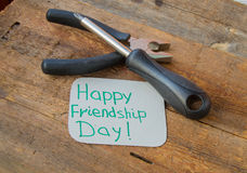Tags happy friendship day and tools on the old wooden background Royalty Free Stock Photography