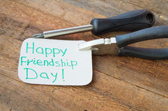 Tags happy friendship day and tools on the old wooden background Stock Photography
