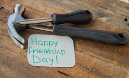 Tags happy friendship day and tools on the old wooden background Royalty Free Stock Images