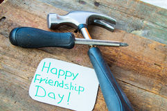 Tags happy friendship day and tools on the old wooden background Royalty Free Stock Photo