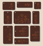 Tags, labels, flowers, leaves on a brown background. Royalty Free Stock Image