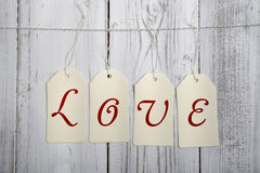 Tags with writing love hanging on ribbon, wooden wall Royalty Free Stock Photos