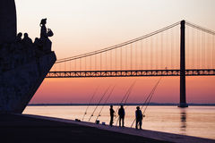 At the Tagus river in Lisbon. Angler silhouettes with the memorial of discoveries at the Tagus river in Lisbon, Portugal royalty free stock photo