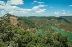 Tagus River running through a valley with hills covered by trees. In a sunny day at the Monfrague National Park. A remarkable place with a beautiful ridge and royalty free stock images