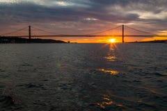 Tagusrivier, Brug 25 April Lissabon bij zonsondergang van schip, Portugal Stock Afbeelding