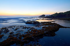 Tanah Lot Temple and ocean waves at sunset Stock Images
