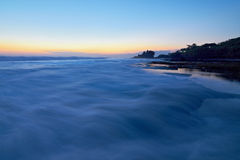 Tahah Lot Temple and ocean waves at sunset Stock Photos