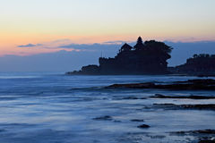 Tahah Lot Temple and ocean waves at sunset Royalty Free Stock Photos