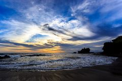 Tahah Lot Temple and ocean waves at sunset, Bali Royalty Free Stock Photo