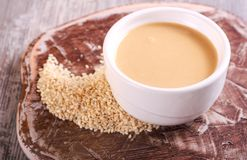 Tahini paste - sesame sauce. On wooden board royalty free stock photography