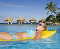 Tahiti - Girl on an airbed. Girl on an airbed in a tropical resort in Tahiti in the South Pacific Ocean stock images