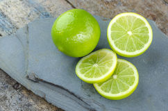 Tahitian limes on a stone . Stock Images