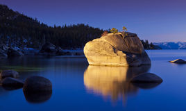 Tahoe Twilight. Sunset at Bonsai Rock, Lake Tahoe, Nevada.  Large granite boulders reflecting into glassy water with warm light Stock Photography