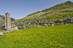 Tahull village in Valley of Boi in Catalonia. Tahull village landscape with green meadow covered with yellow dandelion flowers is t foreground, Famous saint Royalty Free Stock Photography