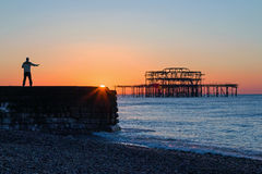 Tai Chi and Brighton Sunrise. Person practicing Tai Chi at sunrise near West Pier, Brighton Royalty Free Stock Photography