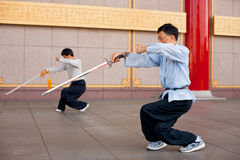 Tai Chi Chuan Crouch. Taipei - August 13, 2011: Two men crouch with legs crossed in unison in a Tai Chi Chuan stance.  Tai Chi is an ancient martial arts popular Royalty Free Stock Photo