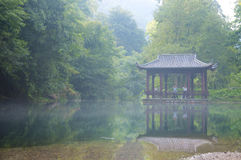 Tai Chi Couple. A couple practicing Tai Chi in an Asian style gazebo near a misty covered body of water Stock Photography
