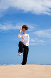Tai chi in the dunes. Young woman in black and white making tai chi moves Royalty Free Stock Image