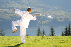 Tai Chi exercise with  sword in nature on green field Stock Photo