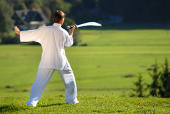 Tai Chi exercise with  sword in nature on green field Royalty Free Stock Images