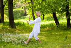 Tai chi. Good looking senior woman in the park Royalty Free Stock Image