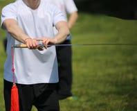 Tai Chi martial arts athlete expert makes motions with sword. Tai Chi martial arts athlete expert makes motions with sharp sword Royalty Free Stock Image