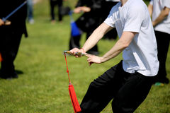 Tai Chi martial arts athlete makes motions with sword Royalty Free Stock Photos